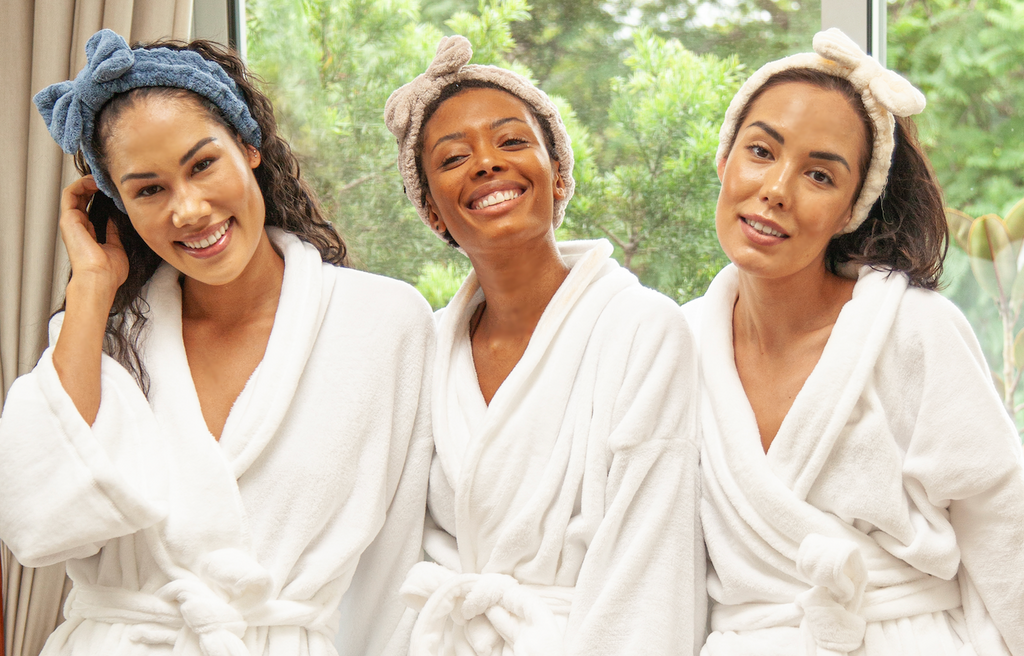 three attractive women smiling in white robes