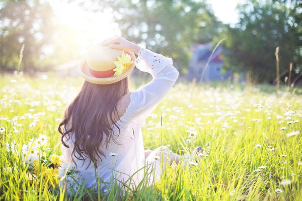 woman with black long hair sitting in a field under sun holding her hat