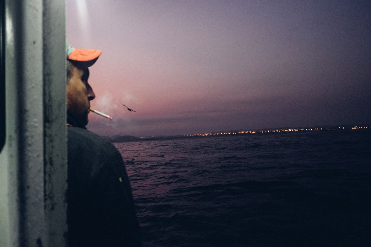 A fisherman at dawn on his boat. August 2016