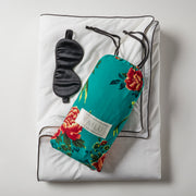 Open Road Portable Throw Set comes with a throw in white with black piping, carrying pouch, and mulberry silk eye mask