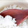 Closeup image of a Red Hardwood Rice Spoon in white rice