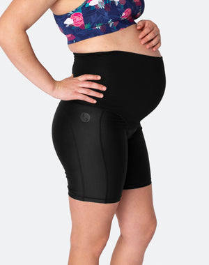 pregnant woman wearing black high waisted bike shorts over the bump