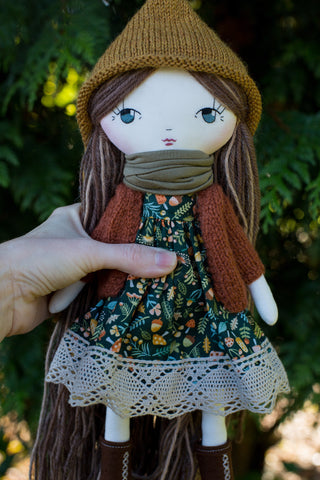 handmade cloth doll wearing mushroom dress, pixie hat and rust cardigan