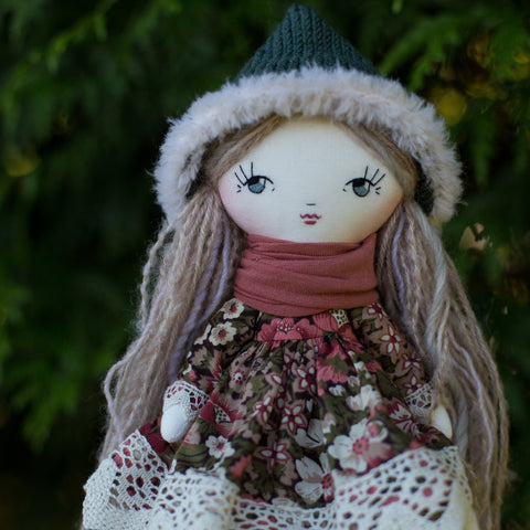 handmade cloth doll wearing vintage floral fabric dress and fur trimmed pixie hat