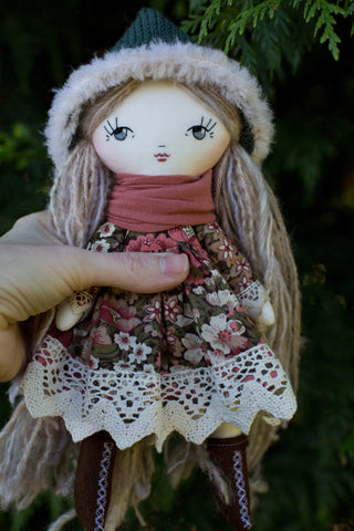 handmade cloth doll wearing vintage floral dress with lace and fur trimmed pixie hat