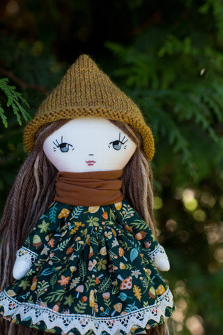 handmade cloth doll wearing mushroom dress and pixie hat