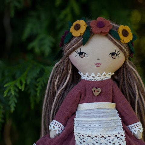 handmade cloth doll in autumn dress, lace apron and flower headband