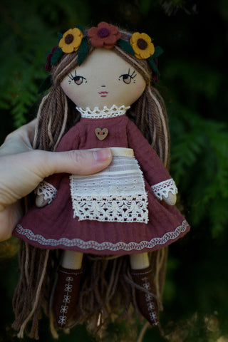 handmade cloth doll wearing autumn dress and lace apron with flower headband