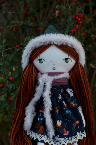 Handmade cloth doll wearing forest dress and fur pixie hat