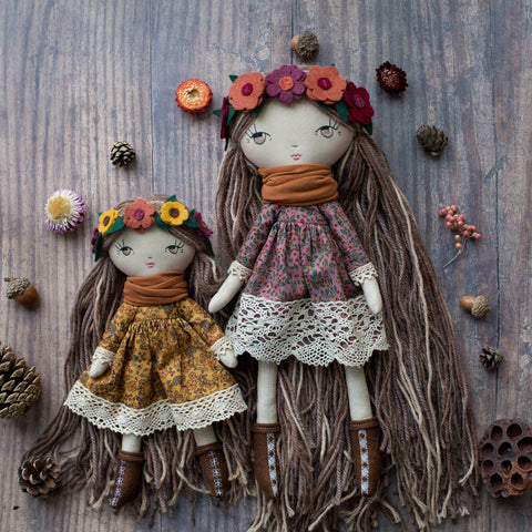 handmade cloth doll wearing autumn floral dress and flower headband