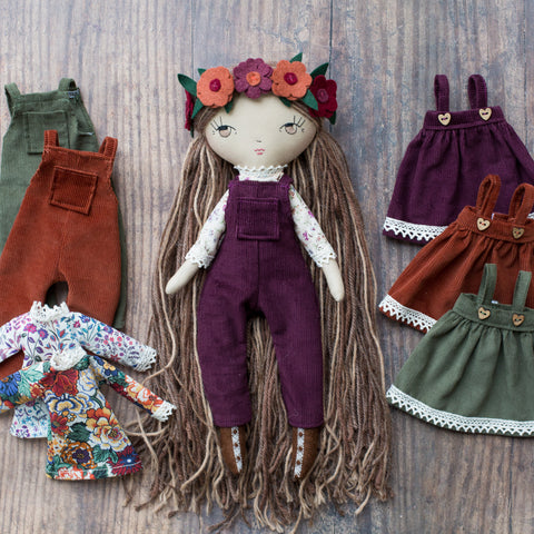 handmade cloth doll wearing dungarees and pinafore