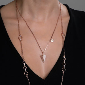 Silver heart shape pendant necklace on neck of a model.