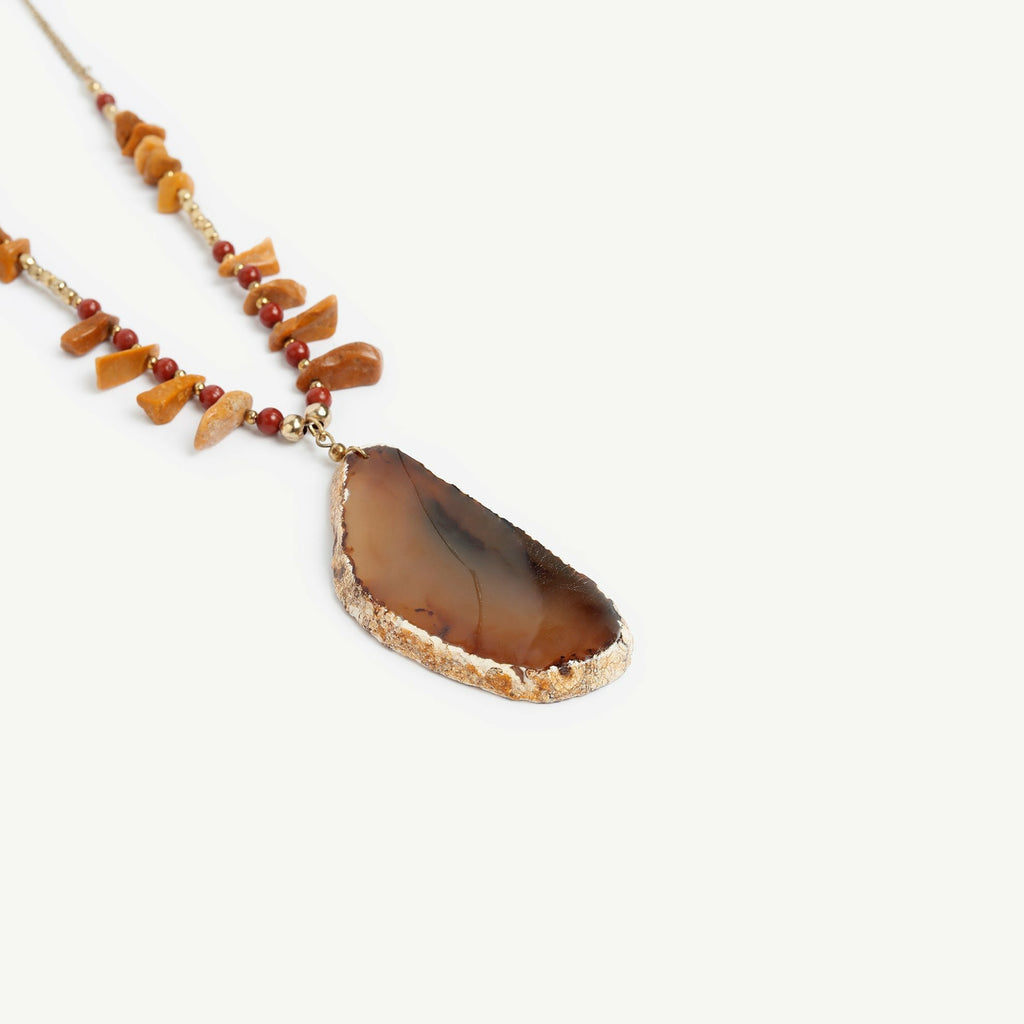 Brown natural stone necklace with small beads and a bigger pendant attached to a metal chain.