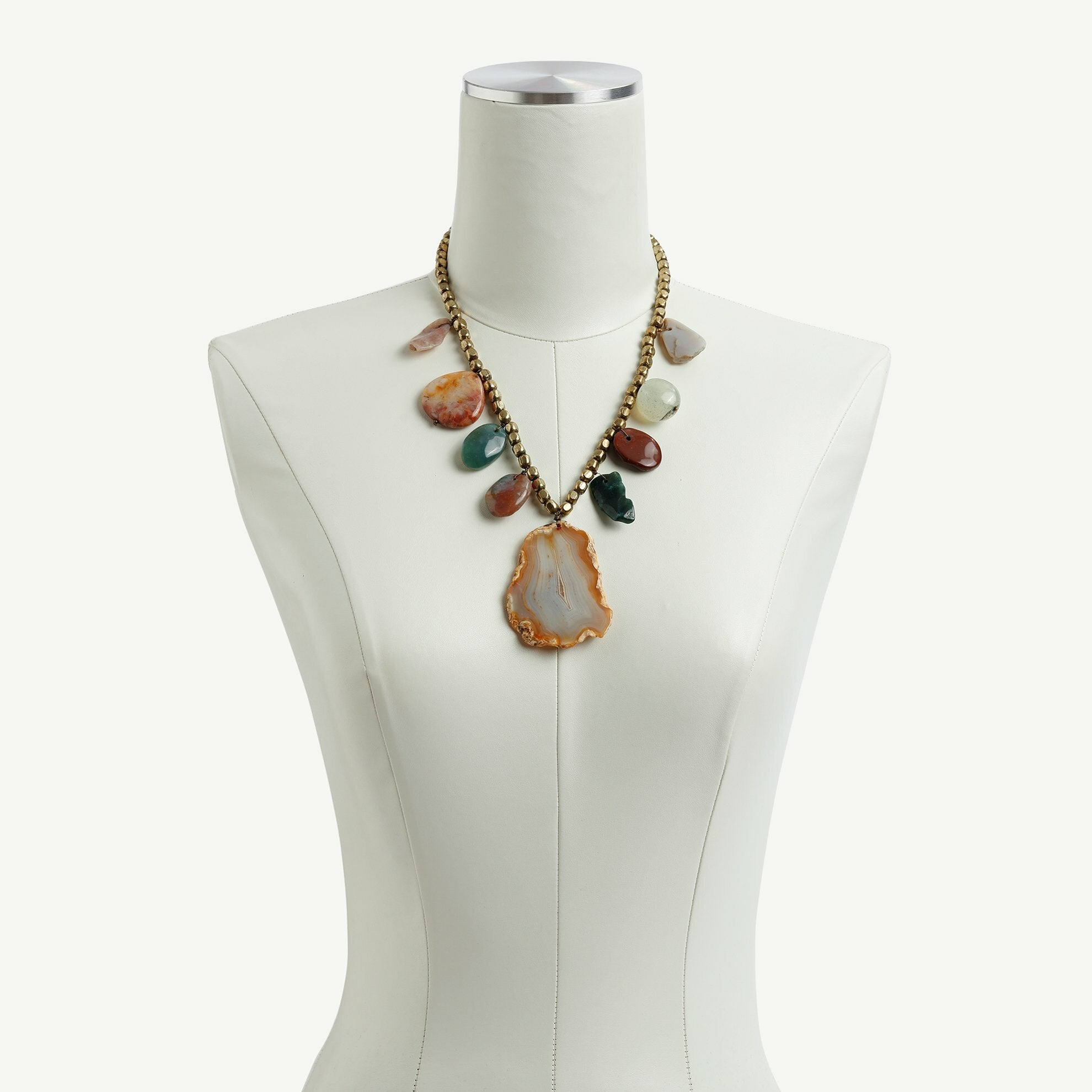 Natural stone necklace on dress form.