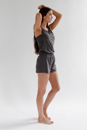 A brunette woman wearing a charcoal grey colored tank top and short