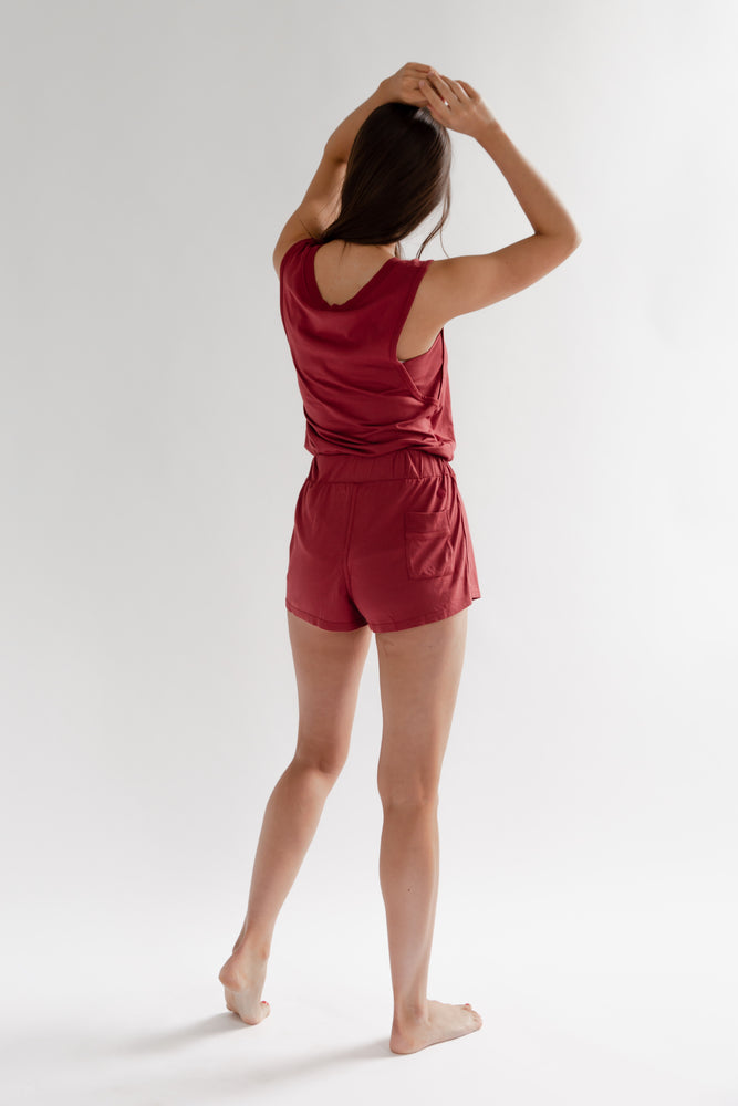 A brunette woman wearing a sleepwear outfit featuring a muscle tank with underarm panel and short made of supima cotton