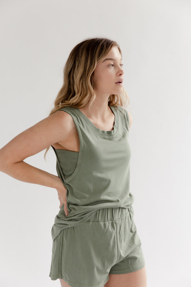 A blonde woman with her hands on her hips wearing a sage green muscle tank top and short made of supima cotton