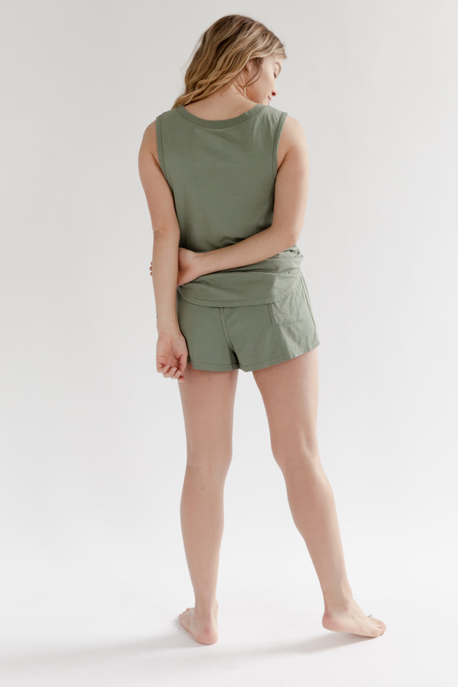 A blonde woman wearing a sage green muscle tank top and short made of supima cotton