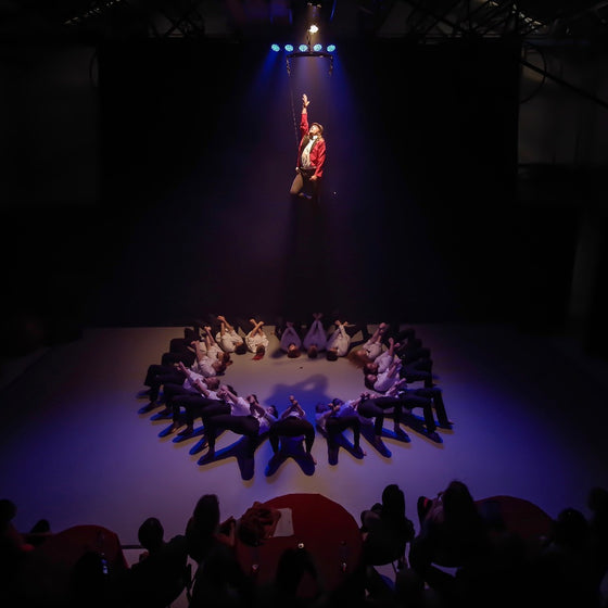 A circle of performers lie on stage, a man is lifted in air with a harness