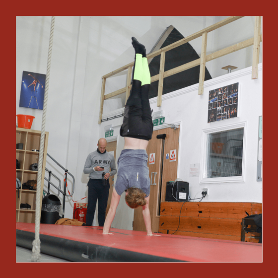 acrobatics student performs a handstand forwards roll on a red mat