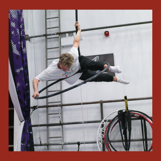 aerial hoop student performs a move from the top of the hoop