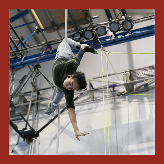 aerial rope student holding an upside down position on a white rope