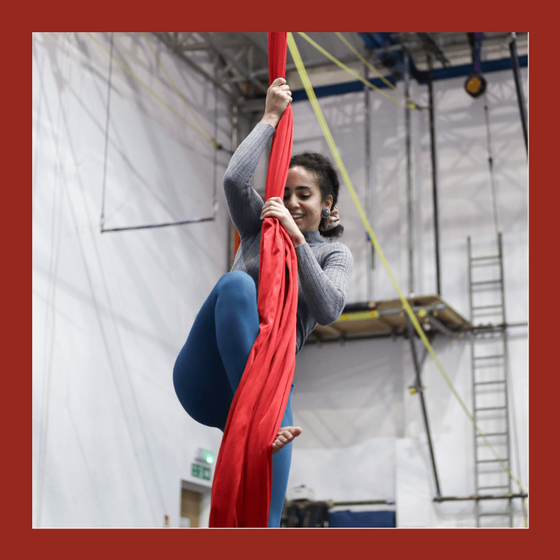 aerial silks student climbs onto red silks
