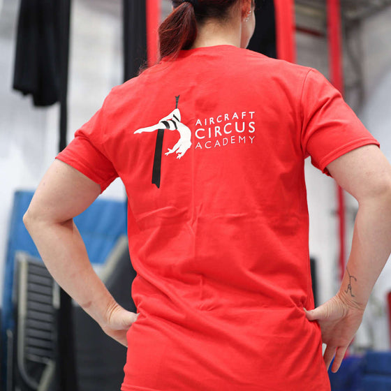 Circus student faces away from the camera to show the back of her AirCraft Circus Academy tshirt
