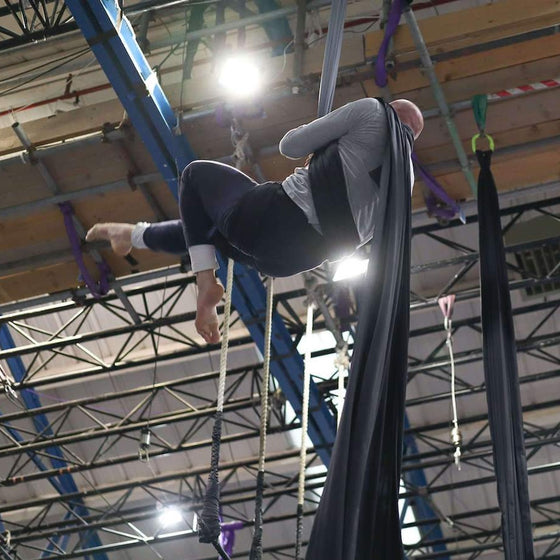 Aerial silks student prepares to perform a drop on silks