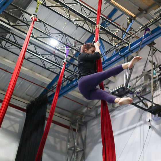 Aerial silks student holds a straddle position whilst hanging from the silks