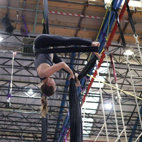 Aerial silks student upside down in a wrap on silks