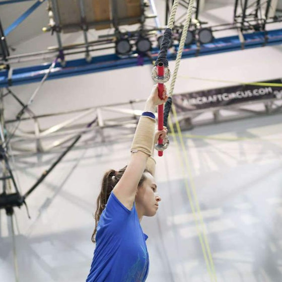 Trapeze student standing underneath the bar