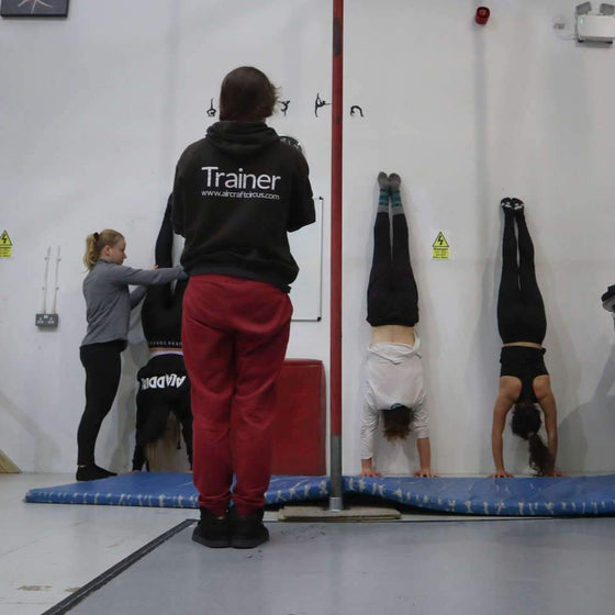 Handstand students holding handstands facing the wall