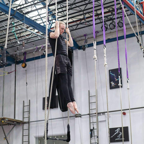 Trapeze student doing a pull up in the trapeze ropes
