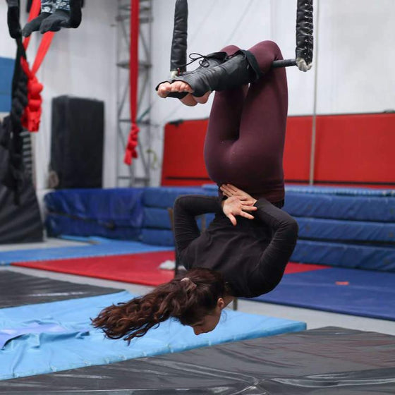 Trapeze student in a knee hang