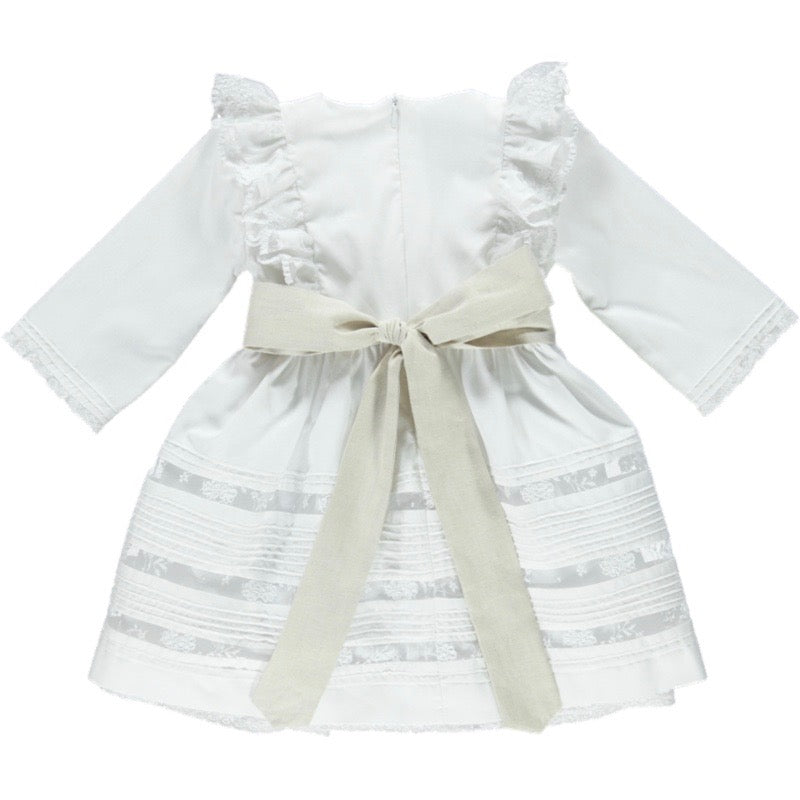 Back view of white flower girl dress with lace panels and shoulder frills. tie bow fastening