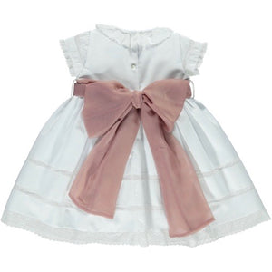 back of white ceremony dress with short sleeves and large pink tie bow