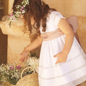 girl wearing white ceremony dress with pink waistband and lace cut outs to skirt