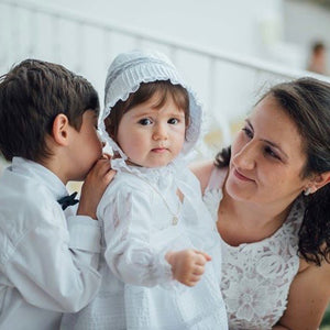 baby wearing white ceremony dress with white matching bonnet. made in Portugal