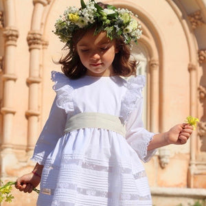 girl wearing white flower girl dress with lace panels and shoulder frills.