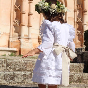 Back view of girl wearing white flower girl dress with lace panels and shoulder frills and a tie bow
