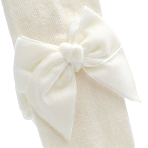 close up of velvet bow on ivory spanish baby tights