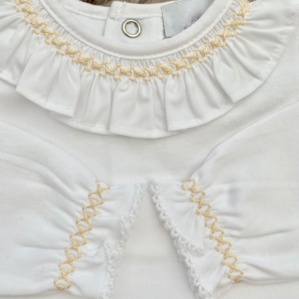 close up of white frill collar bodysuit with beige x stitch to collar and cuffs.  made in Portugal by laivicar