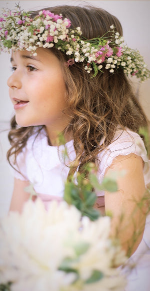 close up of girl wearing white ceremony dress with short sleeves and lace collar