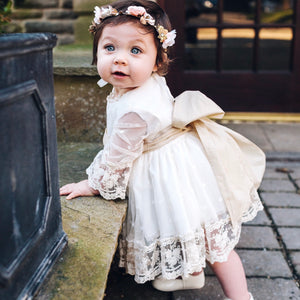 baby girl wearing spanish lace puffball dress showing tie bow at the back