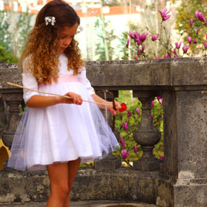 girl wearing white dress with pink sash and tulle flared skirt. hand made in Portugal