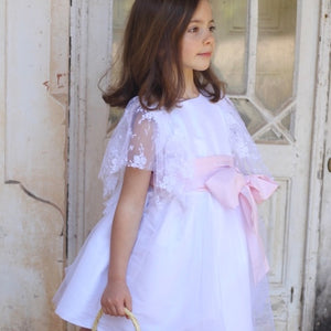 girl wearing white dress with lace fluted sleeves and pink sash. tulle layered skirt