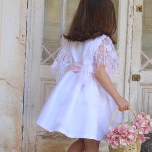 back of girl wearing white dress with lace fluted sleeves and pink sash. tulle layered skirt
