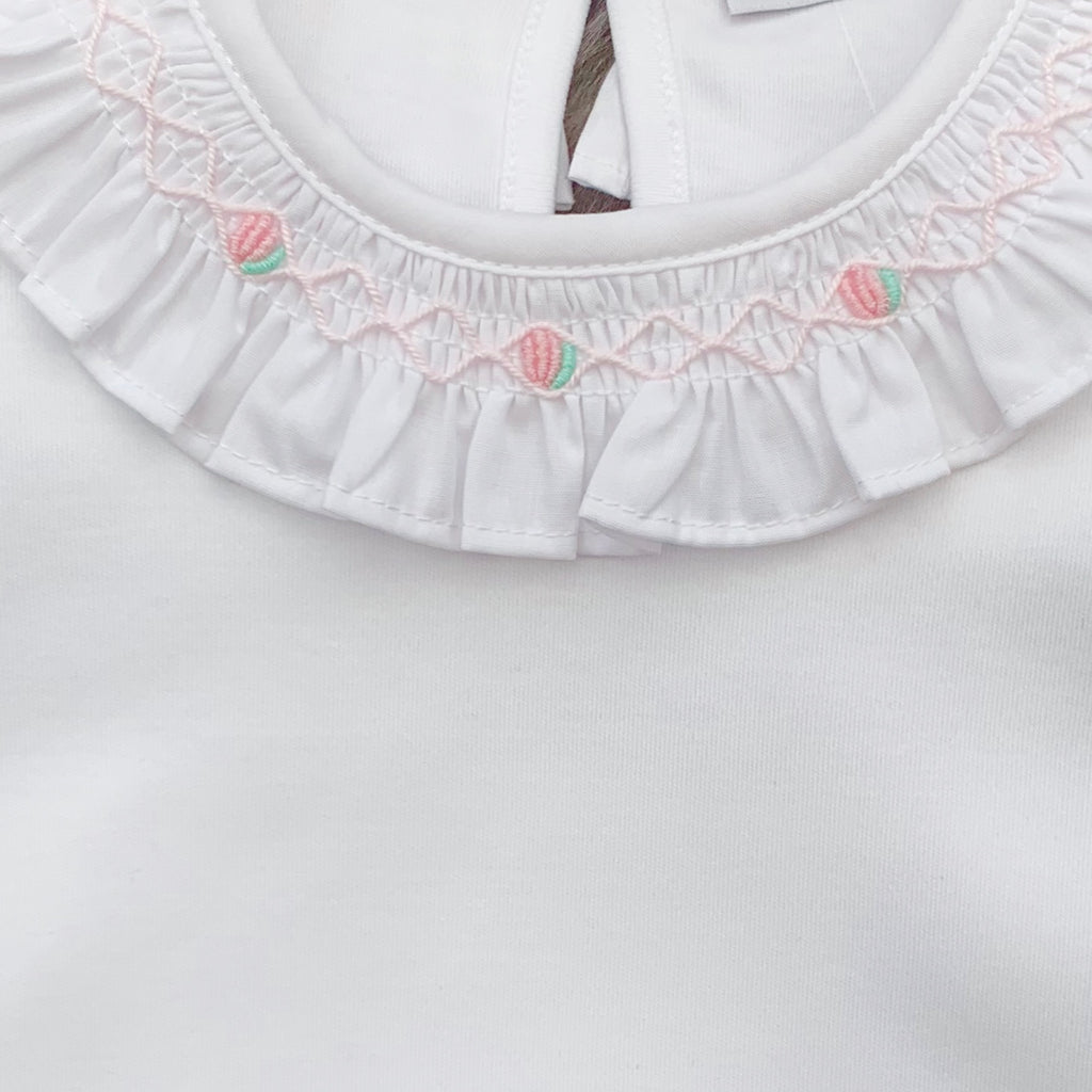 Close up of hand smocked and embroidered frill collar bodysuit.