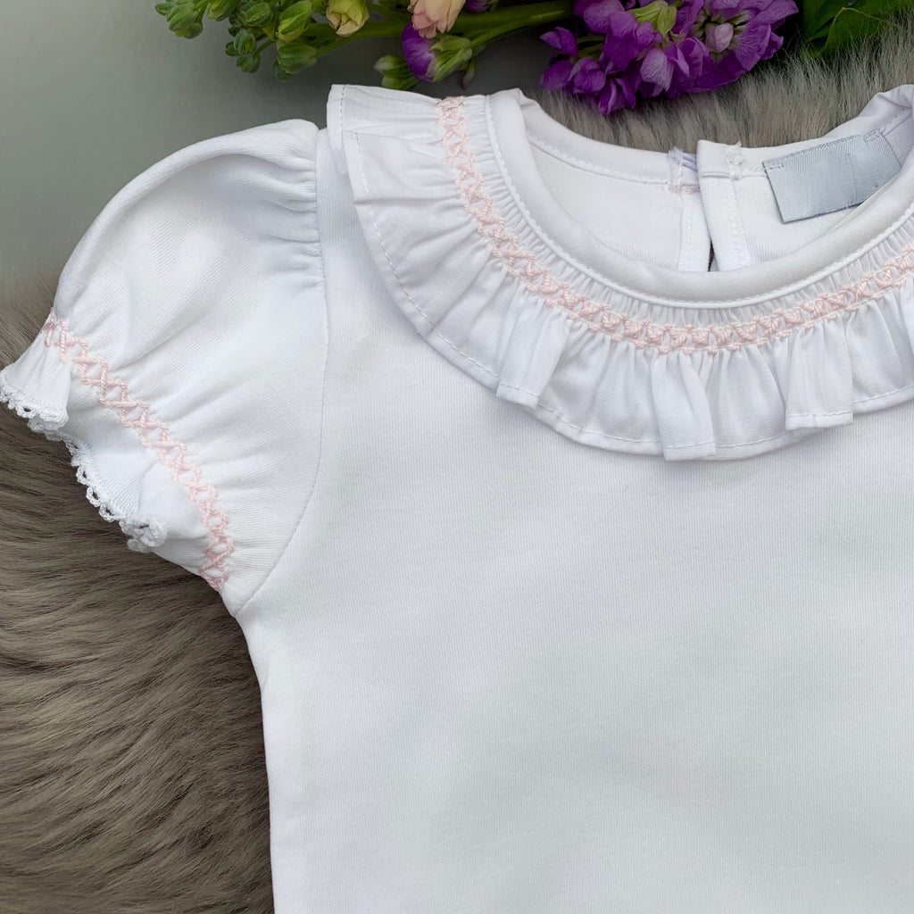 close up of white frill collar bodysuit with pink smocking, made in portugal